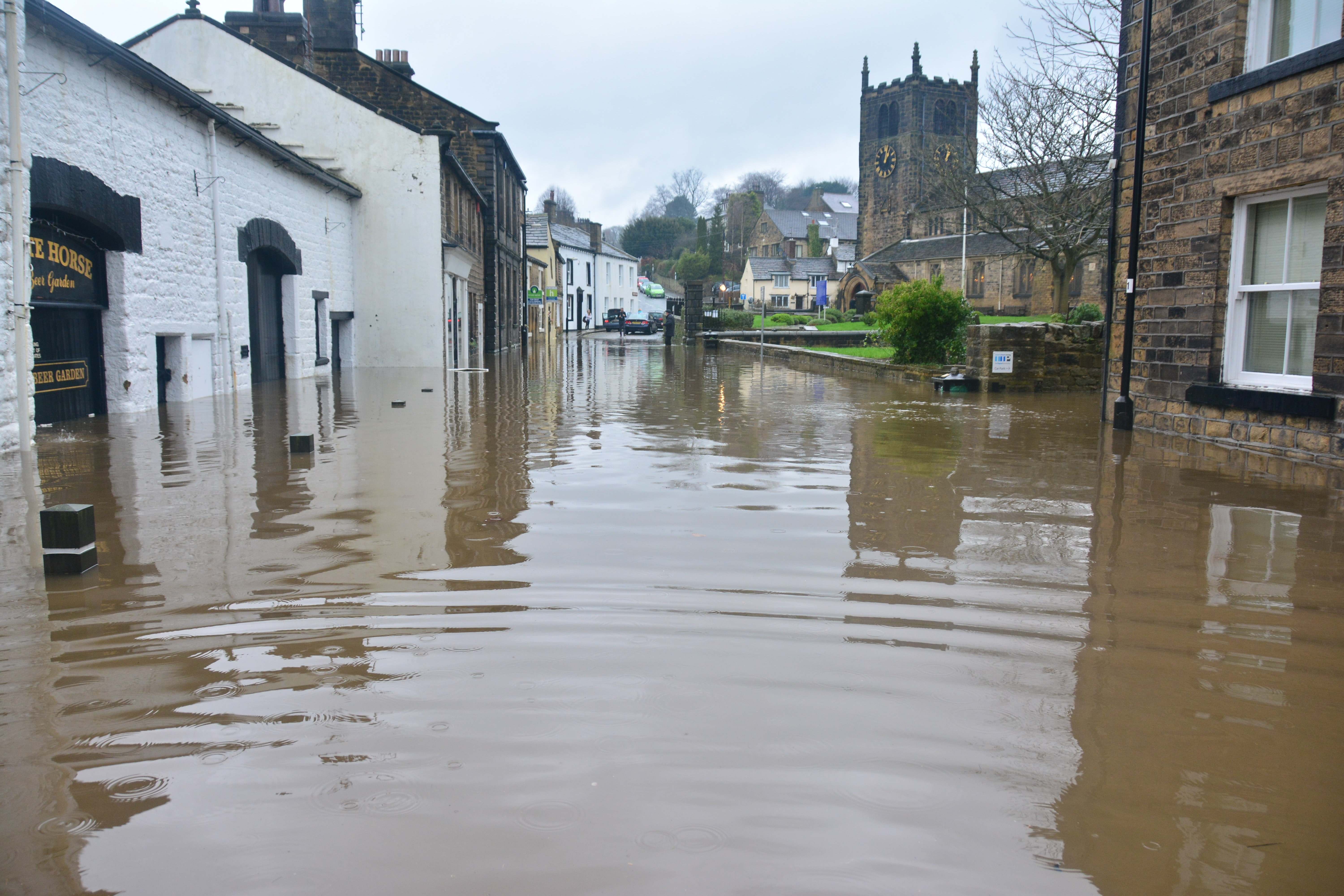 Flooded village street with church at end