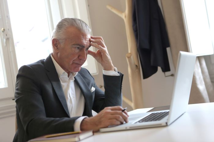 man-in-black-suit-jacket-while-using-laptop-700