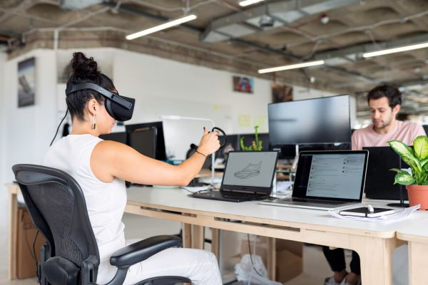 woman-in-white-tank-top-using-black-laptop-computer-with-vr