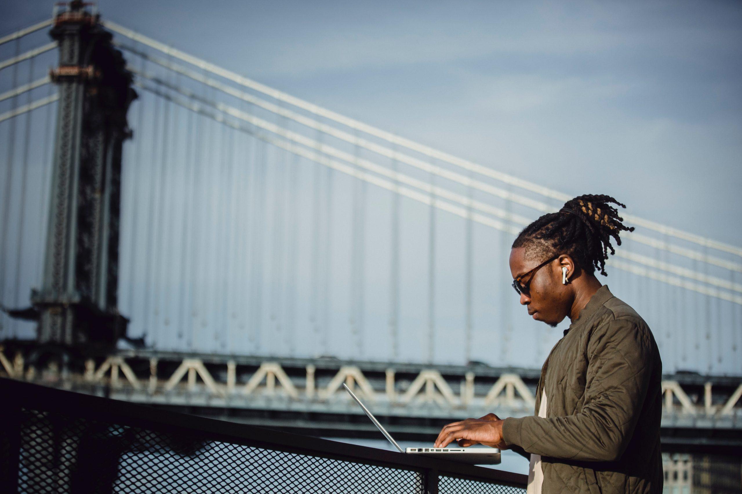 man-at-laptop-by-bridge