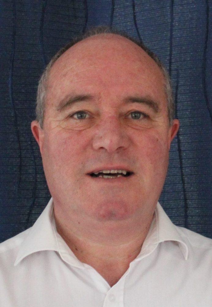 a male in a white shirt against a blue curtain