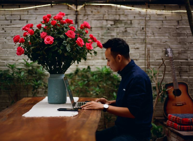 male-in-flower-shop-at-laptop