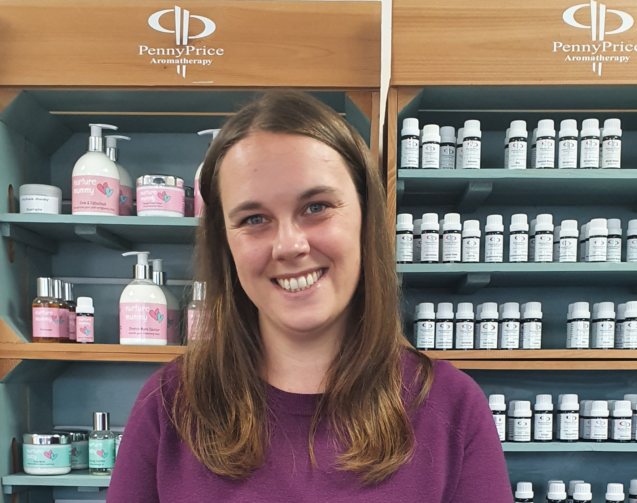A woman with brown hair in a purple top stands in front of aromatherapy products