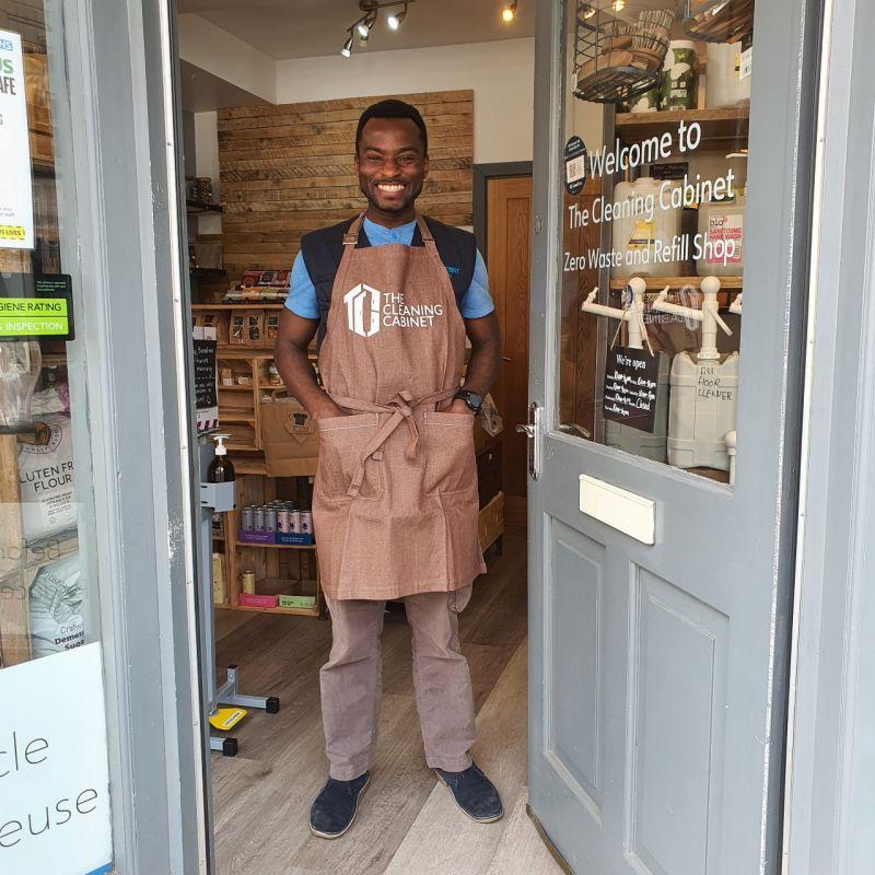a man standing in his shop doorway