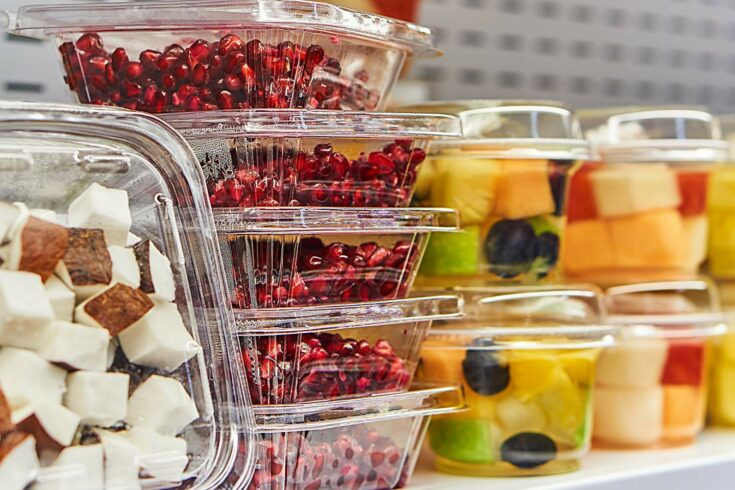Clear plastic boxes containing coconut, pomegranate seeds, and mixed fruit, on a shelf.