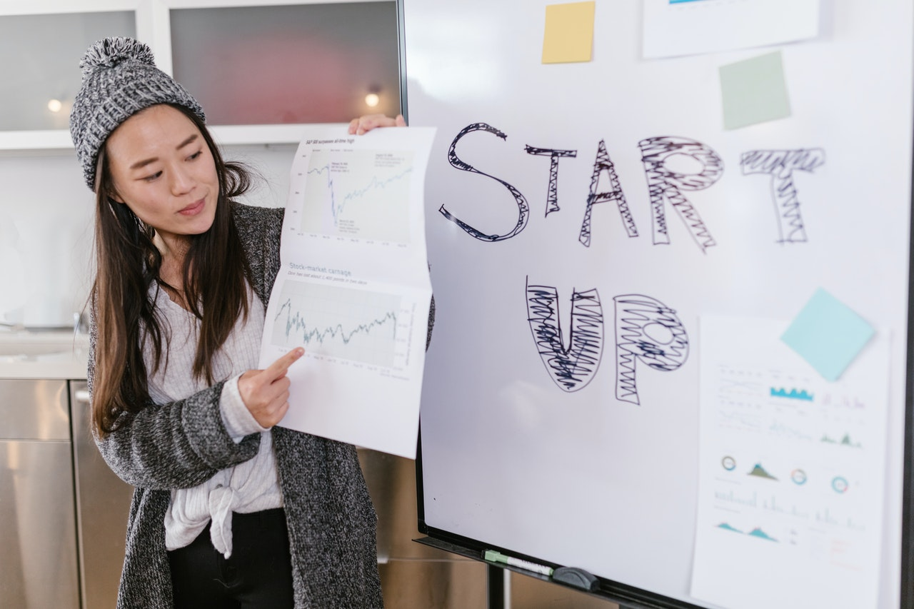 female-presenting-whiteboard-with-startup-words
